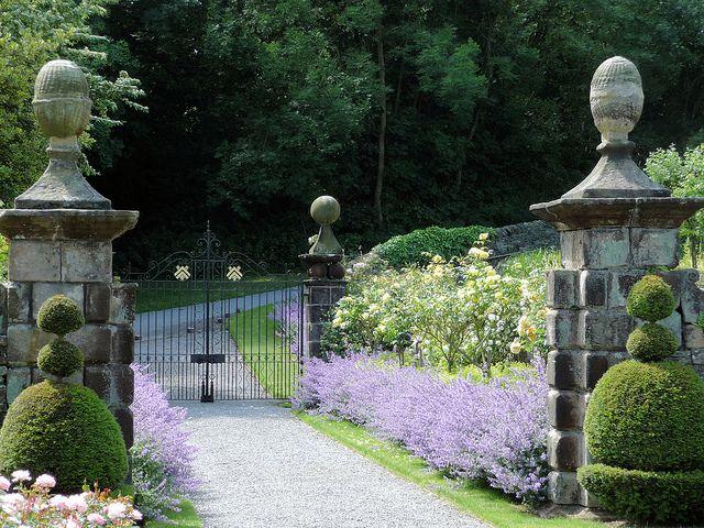 Iron gate + stone pillars + flower lined = beautiful driveway