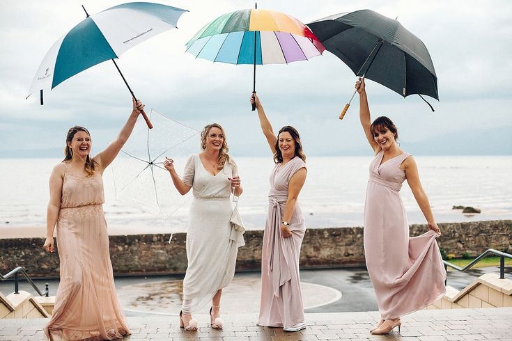 Bride & maids use colourful umbrellas during a summer shower. Image by Katie De Silva Photography