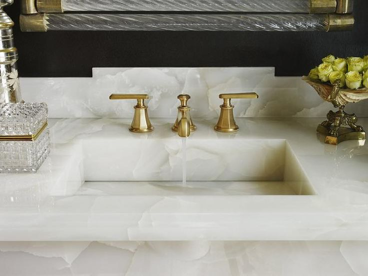 A white onyx vanity top is fitted with a brass faucet kit sat in front of an onyx backsplash and below a glass and brass vanity framed by black walls.