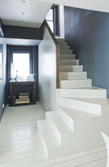 Peinture pour sol Farrow and Ball dans escalier et entrée Sur le béton brut de l'escalier, la même peinture est utilisée après un dépoussiérage et lessivage du support. Réf peinture sol : Off-White No.3 Floor Paint. Peinture bleu des murs : Down Pipe No.26 Estate Emulsion de Farrow & Ball