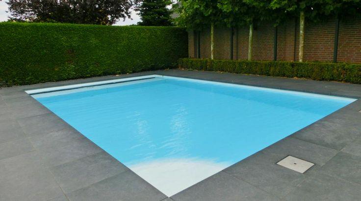 Mooi en bescheiden wit buitenzwembad afgewerkt met grijze tegels