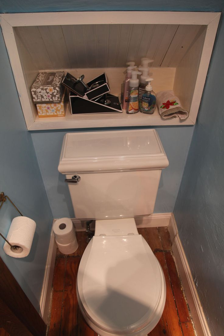 shelf in wall, behind toilet, under stairs
