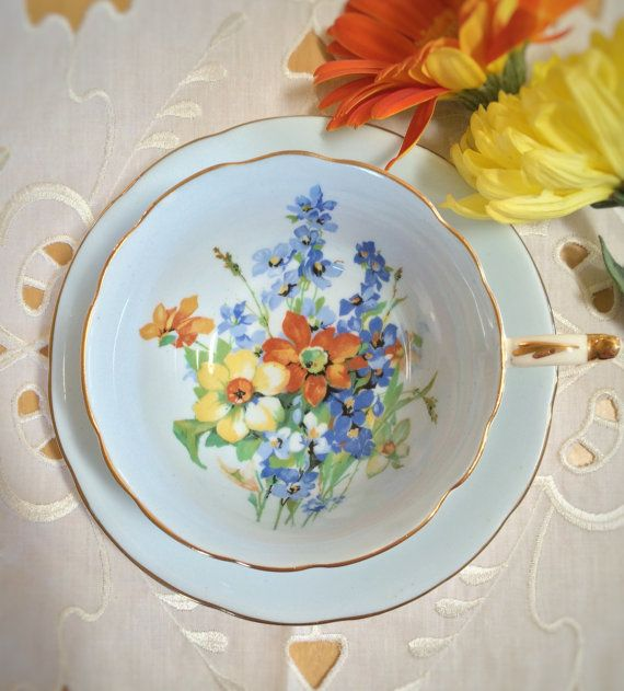 Vintage Paragon teacup and saucer. A pretty and unique color combination on this piece! Baby blue with yellow, orange and blue flowers inside the cup and on the saucer. Fine Bone China – c. 1957+. Nice vintage condition – no chips, cracks, crazing or repairs. Gold gilt is rough in two