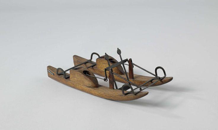 T. van den Bosch | Model van een prototype estafettevaartuig, T. van den Bosch, 1820 - 1858 | Model van een op handkracht voortbewogen catamaran. De twee drijvers zijn met metalen stangen aan de uiteinden aan elkaar verbonden en hebben elk een plaats voor een bestuurder. Het voorbewegingsmechanisme bestaat uit een enkel scheprad met platte contra-gewichten, door middel van handvaten aan elke kant in beweging gebracht.