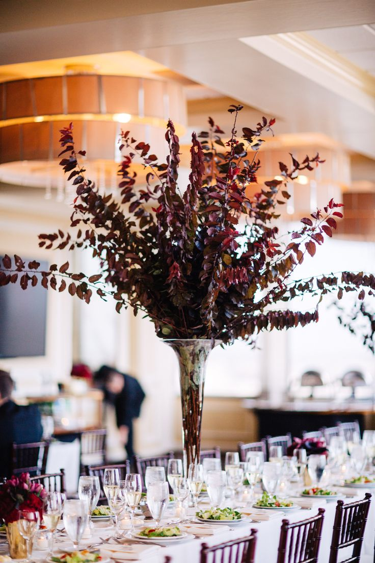 striking and elegant in it's simplicity, this wedding reception tall arrangement of purple plum branches in a clear glass trumpet vase makes an impression.