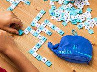 Möbi is a fun, fast-paced tile game that helps kids (and grown-ups) learn and apply basic math skills. Play numbered tiles and symbols to create simple equations. Use all of your numbered tiles first, and you win! Packs away in an adorable blue whale bag, and it's ready to play on any flat surface.