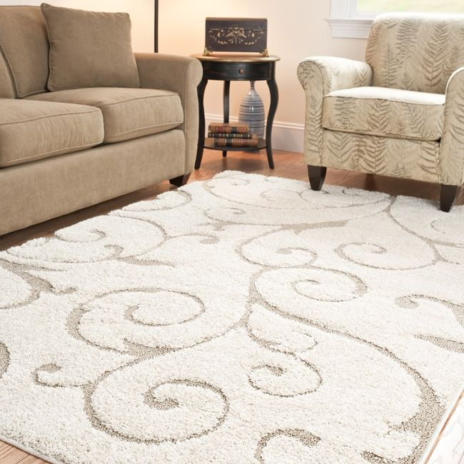 Add a touch of casual design with this ivory and cream power-loomed shag area rug featuring a swirl carving. This rug boasts a plush pile height and lovely neutral hues. Its subdued coloring will go nicely with pre-existing home decor.