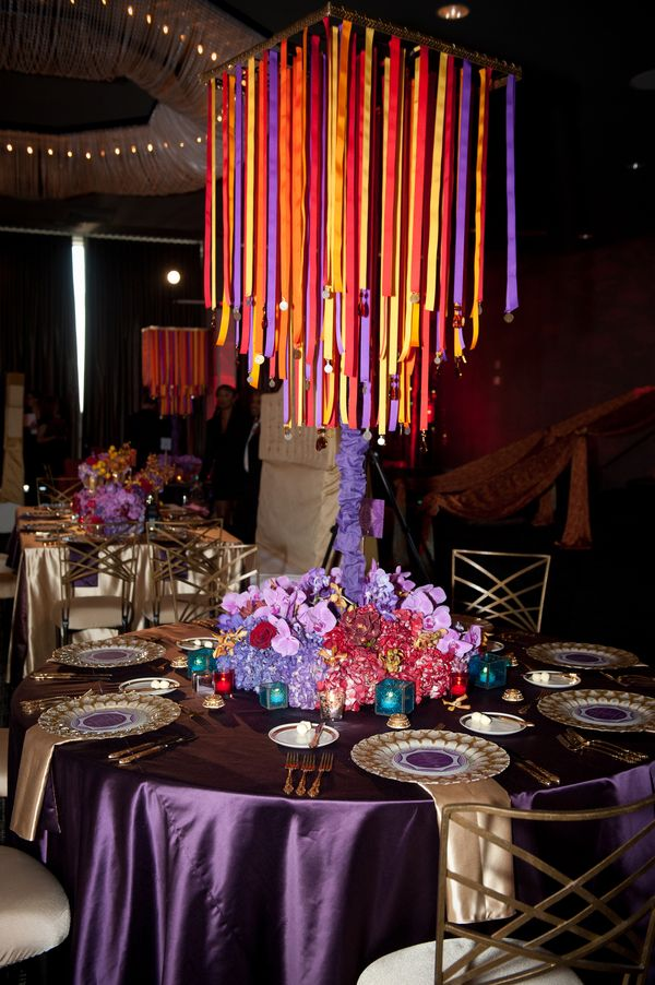 moroccan themed wedding table decor purple and gold with multicolored light streams over top of - Purple Hotel Decor