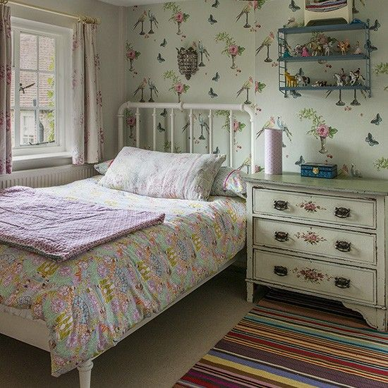 Girl's bedroom with motif wallpaper and iron bedstead