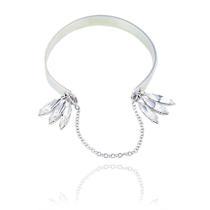 An elegant silver plated cuff with sparkling Swarovski crystal petals and a delicate silver chain clasp. Understated with a brilliant flair. www.jyjewels.com