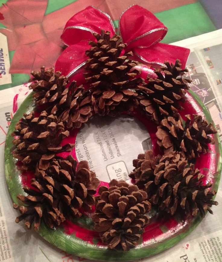 Children's craft made with paper plate, paint and pines cones and ribbon.