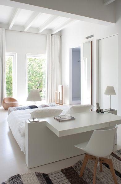 Chambre blanche minimaliste. Tête de lit et bureau à la fois.