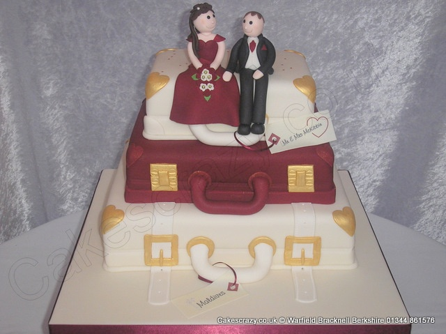 Three tier stacked suitcase shaped wedding cake with bride and groom sugar modelled characters. Finished in alternate ivory and ruby icing with gold hearts and clasps location and name tags