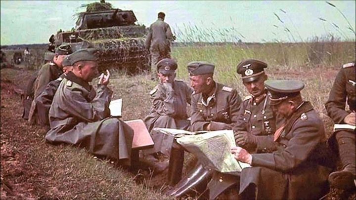 German Generaloberst Heinz Guderian holding a map during a field briefing with his division commanders in Russia in front of a PzKpfw III medium tank summer 1941.
