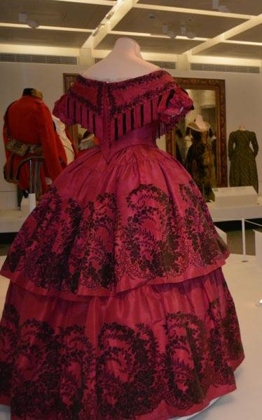 Circa 1860 red and black figured silk evening dress, back view, vioa Glasgow Museums.