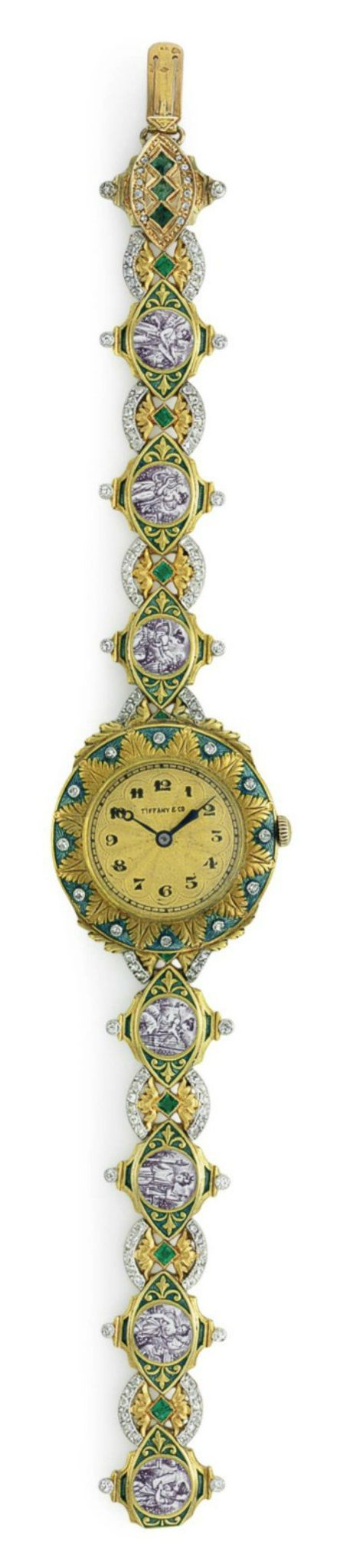 TIFFANY & CO.: AN ANTIQUE ENAMEL, DIAMOND AND EMERALD WRISTWATCH, CIRCA 1910. The circular guilloché dial with black Arabic numerals and blued-steel hands, within a rose-cut diamond, blue guilloché enamel surround, to the sculpted gold and blue guilloché enamel panel bracelet, depicting female mythological figures, enhanced by calibré-cut emeralds and rose-cut detail, with French assay marks for 18k gold, signed Tiffany & Co., with maker's mark for Henri Husson. #Husson #Tiffany #watch…