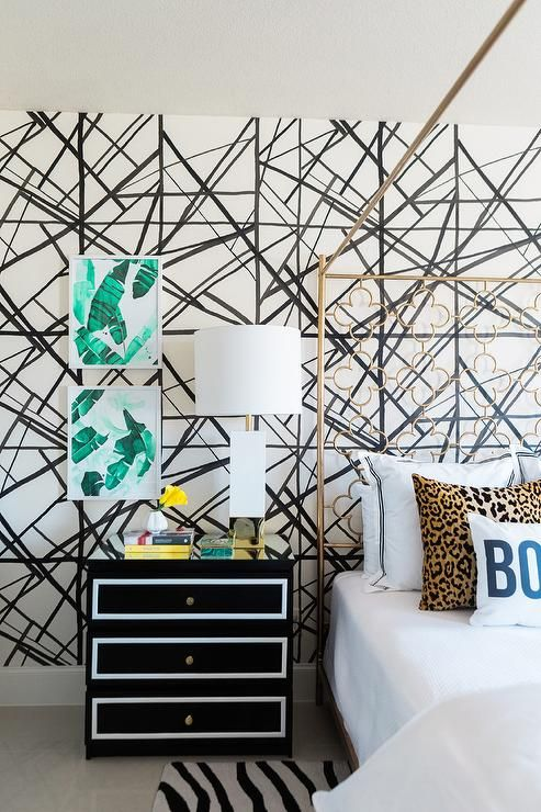 Placed against a Kelly Wearstler Channels wallpapered wall, a black and white nightstand is topped with a Worlds Away Harper Table Lamp and positioned beneath framed banana leaf art.