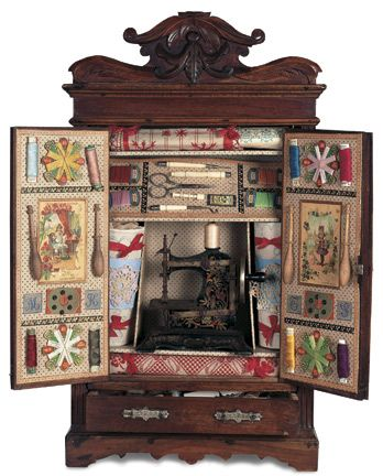 """French Walnut Doll's Sewing Cupboard with Sewing Machine 23"""" Walnut armoire mirrored double front doors has fancily carved crest and apron,and an elaborately fitted interior comprising tin and cast iron toy sewing machine,bobbins,bone sewing tools,samples,lace,threads,and other accessories for teaching needlework to a young child. as seen in French department store Etrennes catalogs. French,circa 1890."""
