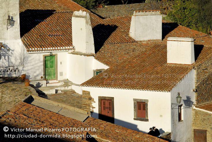 Monsaraz, esencia pura del Alentejo, Reguengos de Monsaraz  Via Ciudad-Dormida | 04.09.2012  La infinita llanura alentejana se eleva de manera extraordinaria en las proximidades del valle del Guadiana. Encaramada en la cumbre de la sierra, la pequeña aldea fortificada de Monsaraz, considerada una de las más antiguas villas de Portugal y una de las siete maravillas del Alentejo, se asoma al Guadiana fronterizo, hoy profundamente transformado por el gigantesco embalse de Alqueva.