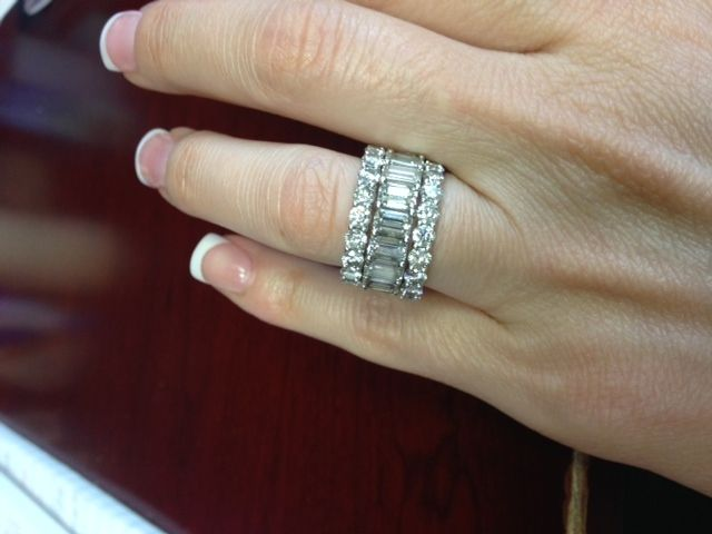 Emerald eternity band sandwiched between two round brilliant bands.