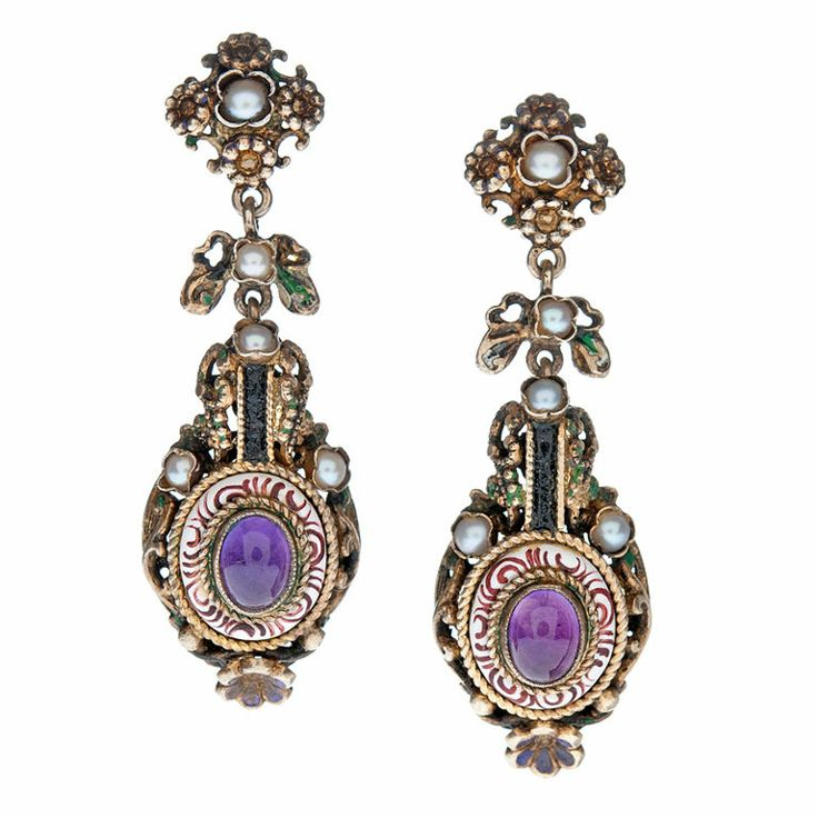 """Striking and unusual Austro-Hungarian long drop earrings. Beautifully handmade in gold over silver, these earrings are the trifecta: Fine make, one-of-a-kind design, and they look gorgeous in their own unique way. In addition fine Amethyst highlight the piece, pairing beautifully with the stylized red & white enamel """"halo"""" encompassing the gems. Furthermore natural pearls sit amongst golden leaves and green enamel work, altogether perfectly complex and suiting."""