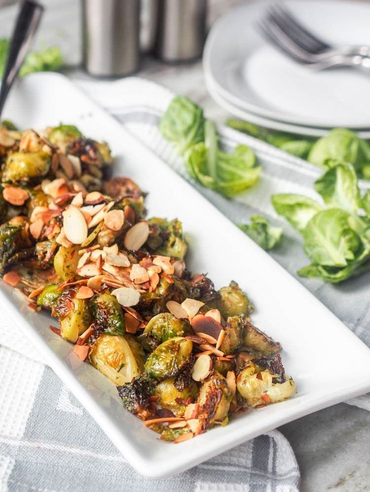 Super simple and healthy 4 ingredient 30 minute side dish: vegan roasted pesto brussel sprouts, topped with crunchy sliced almonds