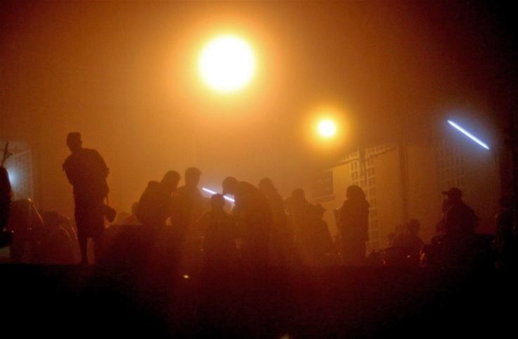 Dockers silhouetted against street lights as fog hangs over Yangon before daybreak