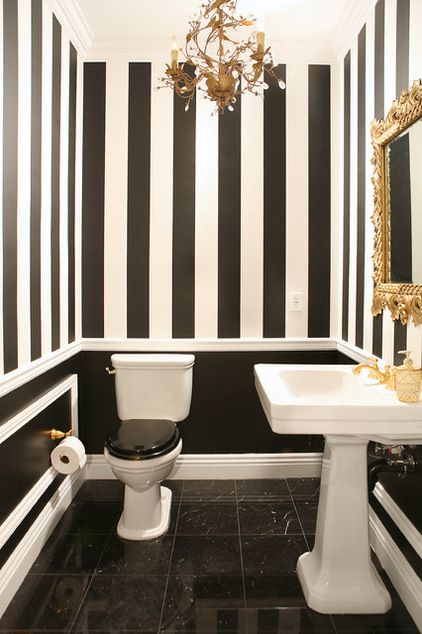 A playfully ornate bathroom takes its black and white seriously. Crisp stripes mix with glossy black paint, elegant marble tiles and over-th...