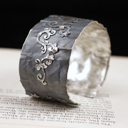 Rough texture contrasts with a floral motif in this cuff bracelet by Agnieszka Hopkowicz.