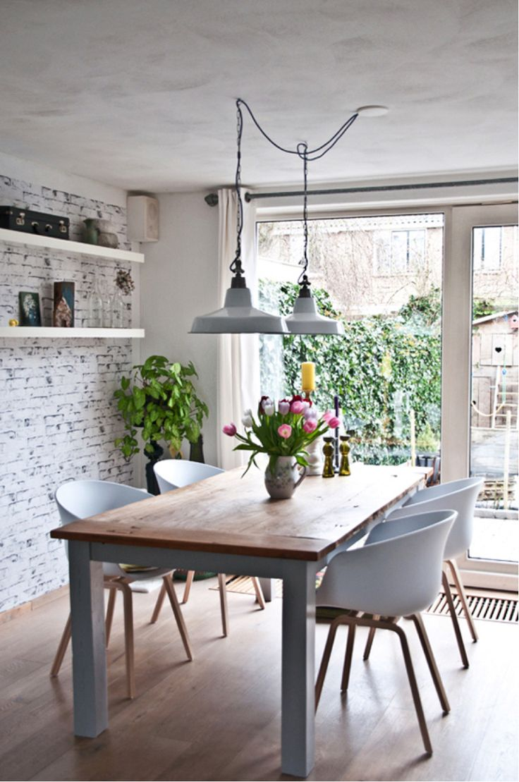 The brick wall painted white and the lights are just perfect for this small dining area project. The simple wooden dining table finishes perfectly the scene! ➤ Discover the season's newest designs and inspirations. Visit us at www.moderndiningtables.net #diningtables #homedecorideas #diningroomideas @ModDiningTables