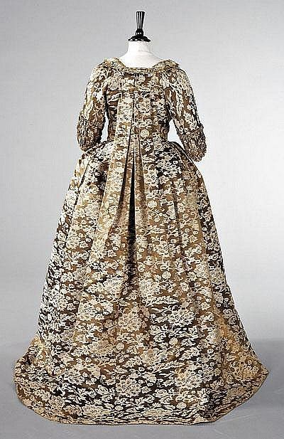 A robe à la Francaise of Chinese lampas satin, circa 1760, The fabric circa 1750, the satin woven with bronze and cream peonies and coiling foliage, the open-robe and petticoat trimmed with furbelows of matching braid trimmed silk, the sleeves with shirred double ruffled `sabot' cuffs, the back panel of the skirt of brown and white. 1740s European silk. #Georgian #1700s #fashion #dress