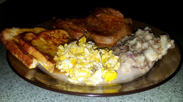 Deep fried pork chops, scrambled eggs,  smothered red taters and french toast.