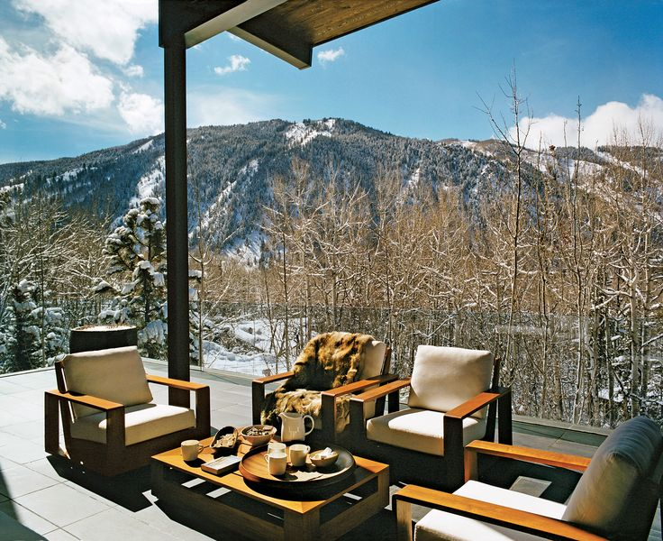 Aerin Lauder's Aspen Home ~ The semi-covered deck, furnished with David Sutherland teak lounge chairs and coffee table with provisions for hot chocolate, overlooks Aspen Mountain.