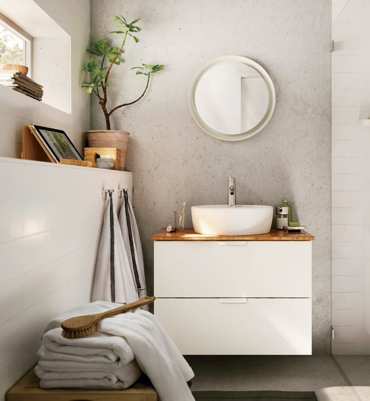 A spa retreat with a round sink and mirror with bamboo countertop and accessories
