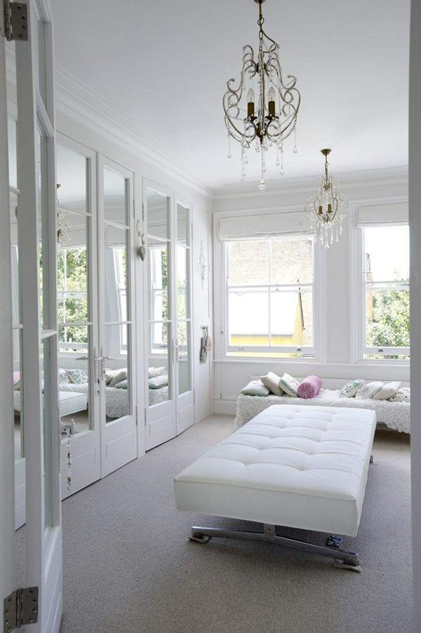 Glamorous Walk In Closet With White Mirrored Doors And Large Light Filled  Windows.
