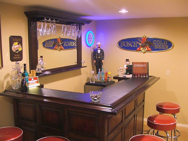 small basement bar love the stain color and layout...Tv behind instead of mirror...beer fridge built in