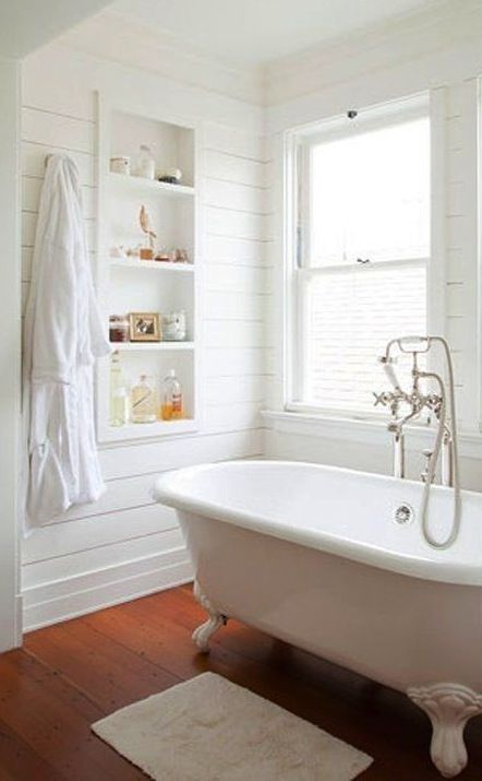 white on white bath with standalone tub, wood floors and shelving nook
