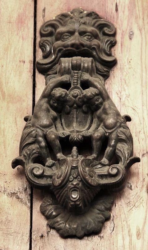 Two cherubs hanging from a lion head door knocker - bronze door decoration from Bologna, Italy