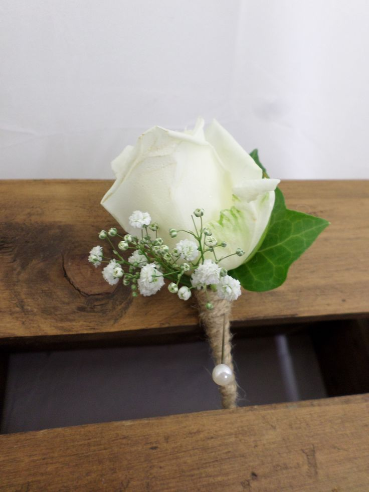 Wedding buttonhole made using a White rose, Ivy and gypsophila. Created by the team at  http://www.floristilene.co.nz/