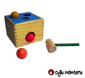 Caja Pelotera.   Moderno juguete de descarga mediante un martillo y 3 pelotas (40 mm.) coloreadas que atraviesan los agujeros y se deslizan por una rampa interna, saliendo por el agujero frontal.  La parte superior presenta un recubrimiento de goma eva lo que le brinda color y funcionalidad al juguete, ideal para desarrollar la motricidad gruesa. Medidas aprox.: 14 x 14 x 11 cm. Edad recomendada: 1 a 3 años