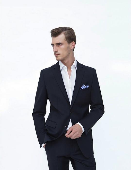 Zara - blazer clásico en color azul marino combinado con pantalón a juego y camisa blanca que se contrasta con el pañuelo de cuadros vichy en color azul dentro del bolsillo relojero.