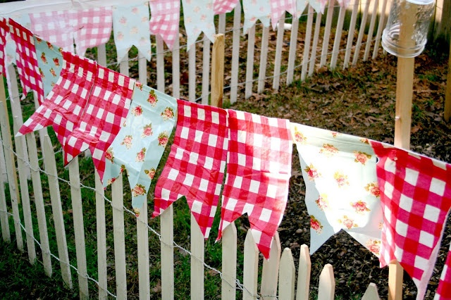 garden bunting made from rope, duct tape and vinyl tablecloth. mounted to wooden stakes around garden edge,