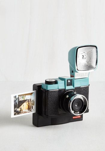 Celebrate the unique, retro style of Lomography with this Diana instant camera! Topped with a turquoise colorblock, this black camera arrives with a reusable flash, colored gel filters, and a hardback book that will bring you up to speed on the Diana's esteemed history - providing everything you need to cultivate your artful aspirations!