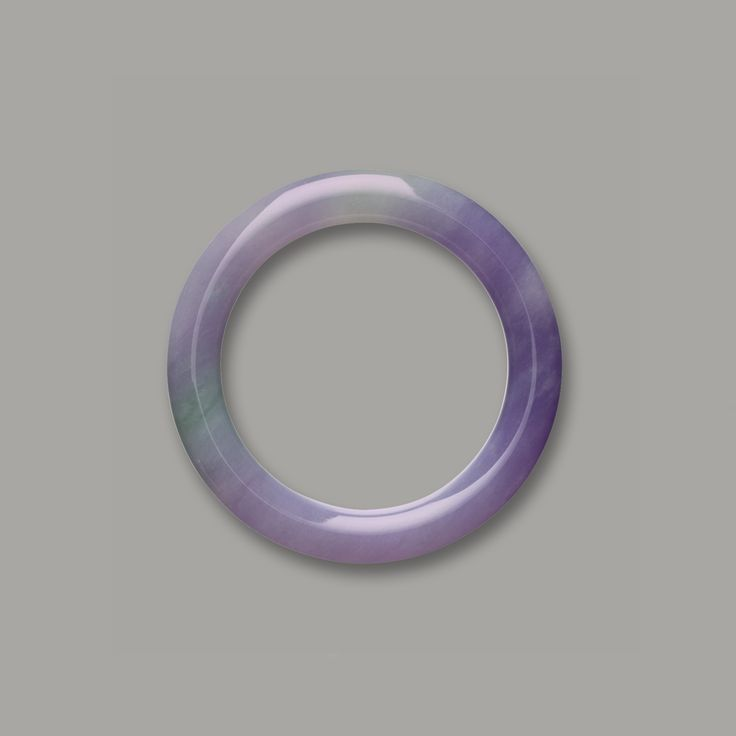 LAVENDER JADEITE BANGLE The translucent jadeite bangle of lavender colour suffused with patches of celadon tone. Inner diameter and thicknes...