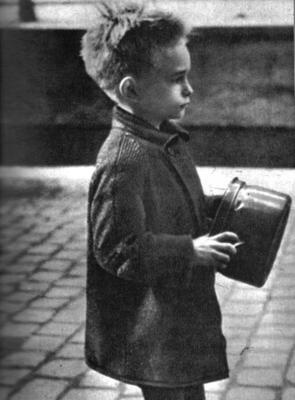 a starving little dutch boy waits patiently for the meal he is about to receive from the canadian soldiers that have liberated his town