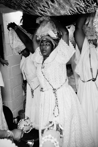 Female priests dance, beckoning the Loas into the containers balanced on their heads. Vodou Ceremonies in Mambo Rose Marie Pierre's Basement Temple Brooklyn, New York, Shannon Taggart 2009 - 2012