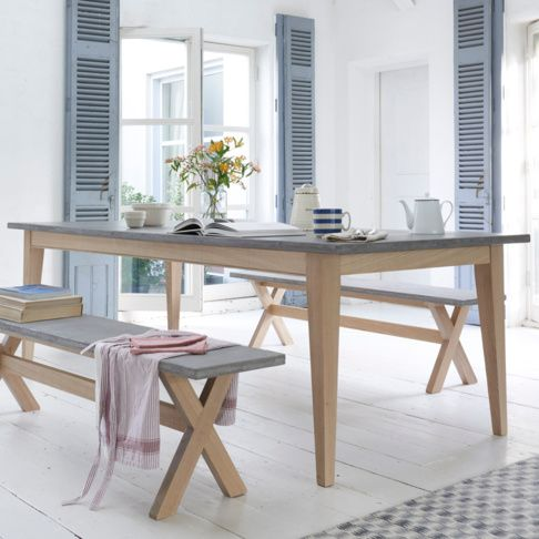 Loaf's stylish new Conker kitchen table has a concrete finish top and sturdy oak legs. Styled here with French grey shutters, white washed walls and fresh flowers.