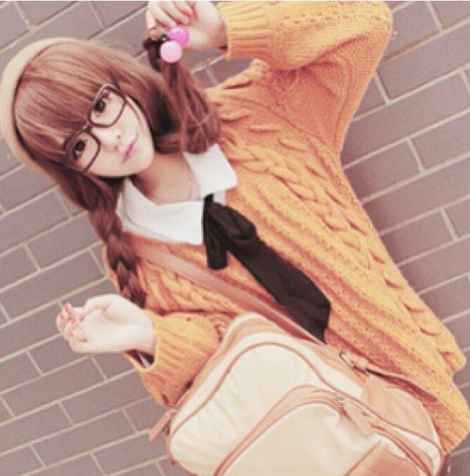 Cute, gyaru: Beige beret. Glasses. White shirt with black ribbon. Orange, cable knit cardigan. Creme backpack.