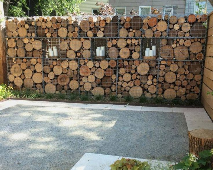 mur en gabion rempli de rondelles en bois et décoré de bougies