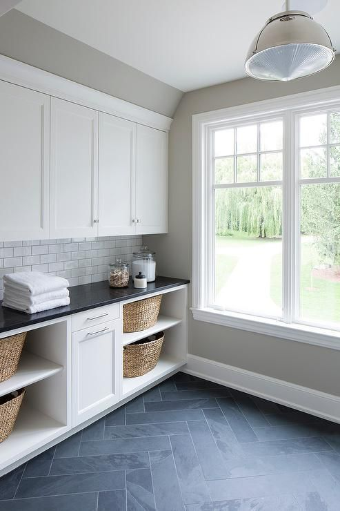 This simple corner in a laundry room is focused on white streamlined cabinetry with open bottom shelves displaying woven storage baskets.